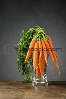 Fresh carrots in a glass vase
