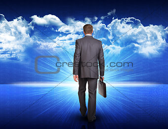 Businessman walking against blue landscape with rising sun