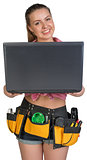 Woman in tool belt, holding opened laptop
