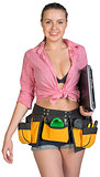 Woman in tool belt, holding laptop under her armpit