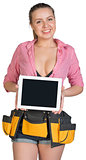 Woman in tool belt showing tablet PC with blank screen