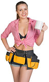 Woman in tool belt showing white mug