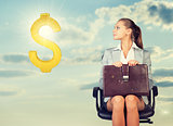 Businesswoman sitting on office chair, looking at dollar sign in the air
