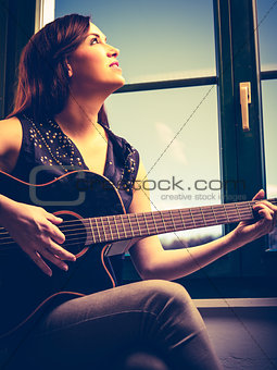 Beautiful woman playing guitar by the window