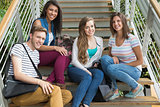 Smiling students sitting on steps