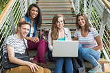Smiling students sitting on steps with laptop