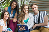 Smiling students sitting on steps with tablet pc