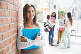 Pretty student smiling and holding notepads