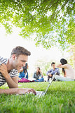 Happy student using his laptop outside