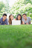 Happy students using laptop outside