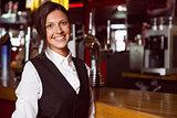 Happy barmaid smiling at camera
