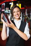 Happy barmaid smiling at camera making cocktail