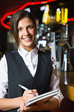 Happy barmaid smiling at camera taking notes