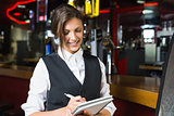 Happy barmaid writing in notepad