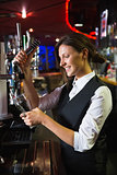 Happy barmaid pulling a pint of beer