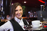 Happy barmaid holding tray with coffee