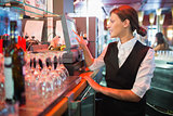 Happy barmaid using touchscreen till