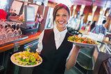Pretty barmaid holding plates of salads