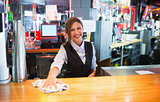 Pretty barmaid wiping down bar