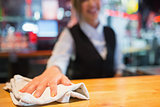 Pretty barmaid wiping down bar