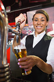 Pretty barmaid pulling pint of beer
