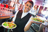 Pretty barmaid holding plates of salads