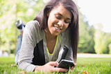Pretty brunette using her smartphone in park
