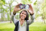Pretty brunette taking a selfie in park