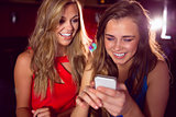 Pretty friends looking at smartphone together