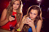 Pretty friends looking at smartphones