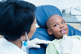 Dentist examining boys teeth in dentists chair