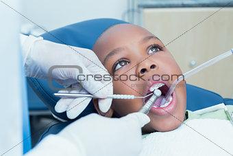 Boy having his teeth examined by dentist
