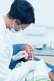 Female dentist examining boys teeth in dentists chair