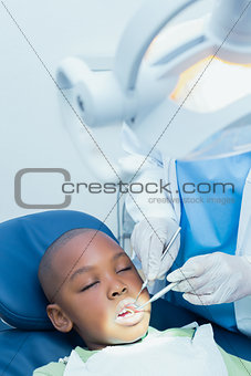 Boy having his teeth examined by dentist