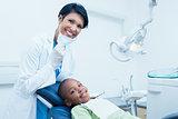 Portrait of smiling female dentist examining boys teeth