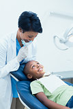 Portrait of smiling female dentist examining boys teeth