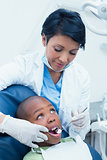 Female dentist examining boys teeth