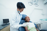 Smiling female dentist examining boys teeth