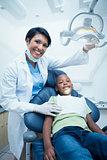 Female dentist examining boys teeth