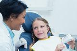 Female dentist teaching girl how to brush teeth