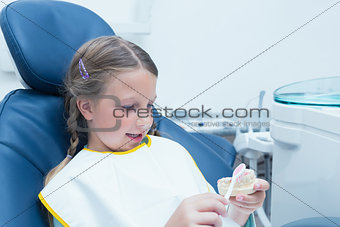 Little girl learning how to brush teeth