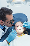 Male dentist examining girls teeth