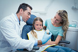 Dentist teaching girl how to brush teeth