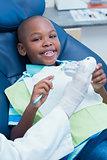 Dentist teaching boy how to brush teeth