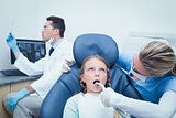 Female dentist examining girls teeth
