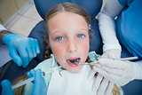 Dentist with assistant examining girls teeth