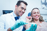 Male dentist teaching woman how to brush teeth