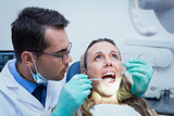 Dentist examining young womans teeth