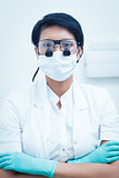 Female dentist wearing surgical mask and dental loupes