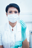 Female dentist wearing surgical mask and gloves